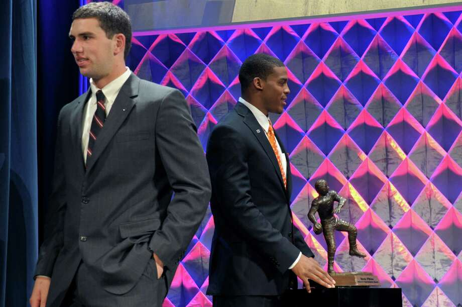 Auburn's Cam Newton, right, poses with the Davey O'Brien Award, after winning the award given to the best quarterback, as Stanford quarterback Andrew Luck leaves the stage at the Home Depot ESPNU College Football Awards in Lake Buena Vista, Fla., Thursday, Dec. 9, 2010.  Newton also won the Maxwell Award, presented to the best all-around player. (AP Photo/Phelan M. Ebenhack) Photo: Phelan M. Ebenhack, ASSOCIATED PRESS / AP2010