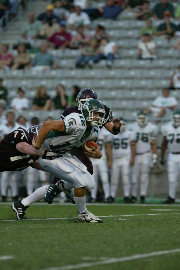 Stratford's #12 Andrew Luck fights to break free from the grasp of Cy-Fair's #77 Craig Drouillard at the Stratford VS Cy-Fair football game at Berry Center on Saturday night Photo: Matthew White, For The Chronicle / Freelance