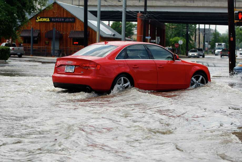 A car tries to navigate Tuesday May 27, 2014, the runoff-flooded intersection of Broadway and Grayson Streets. Photo: William Luther, San Antonio Express-News / © 2014 San Antonio Express-News