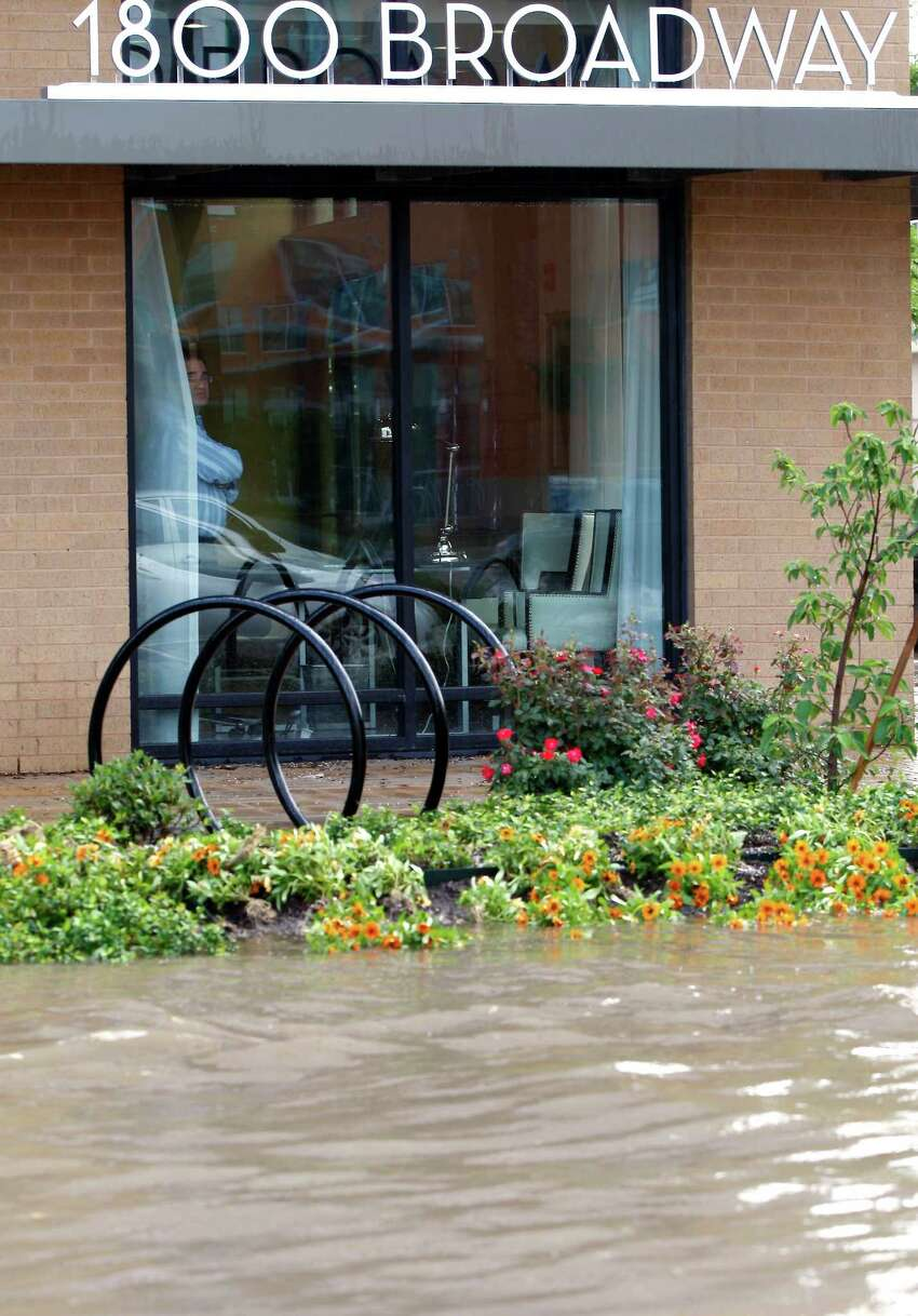 Rain storm runoff floods the Broadway and Grayson Streets intersection Tuesday May 27, 2014.