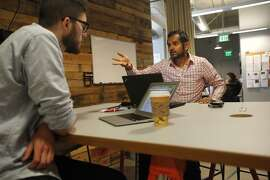 Ross Greenwood, 25, left, and Akash Trivedi, 29, discuss a new pilot program called Project Zip at Kiva May 27, 2014 in San Francisco, Calif. Kiva is a non-profit micro lending company that uses Box.