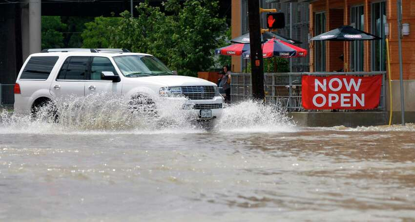 A car tries to navigate Tuesday May 27, 2014, the runoff-flooded intersection of Broadway and Grayson Streets.