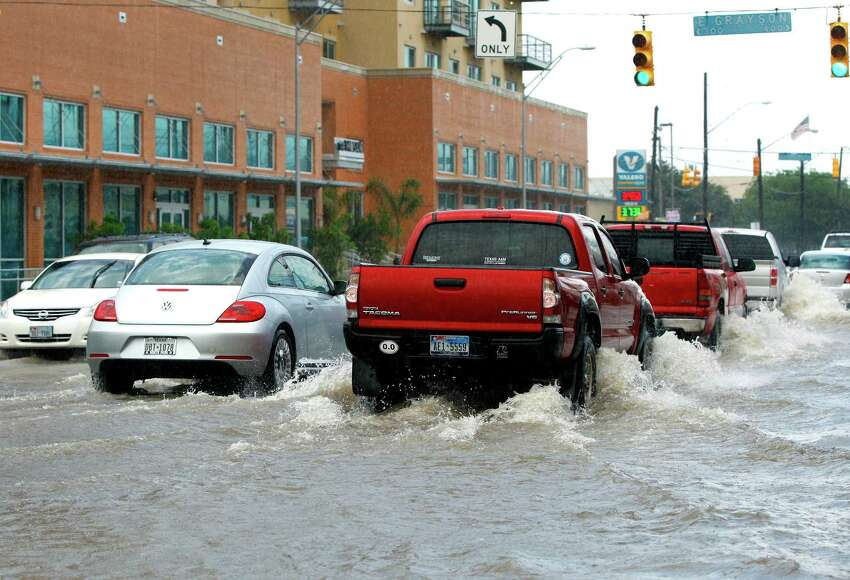 Cars try to navigate Tuesday May 27, 2014, the runoff-flooded intersection of Broadway and Grayson Streets.