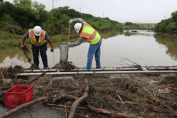 A San Antonio City Public Services crew cleans up debris along Pinn Road at Leon Creek, Tuesday, May 27, 2014. With the heavy rains from Monday's storms, debris accumulated at the low water crossings throughout the area.