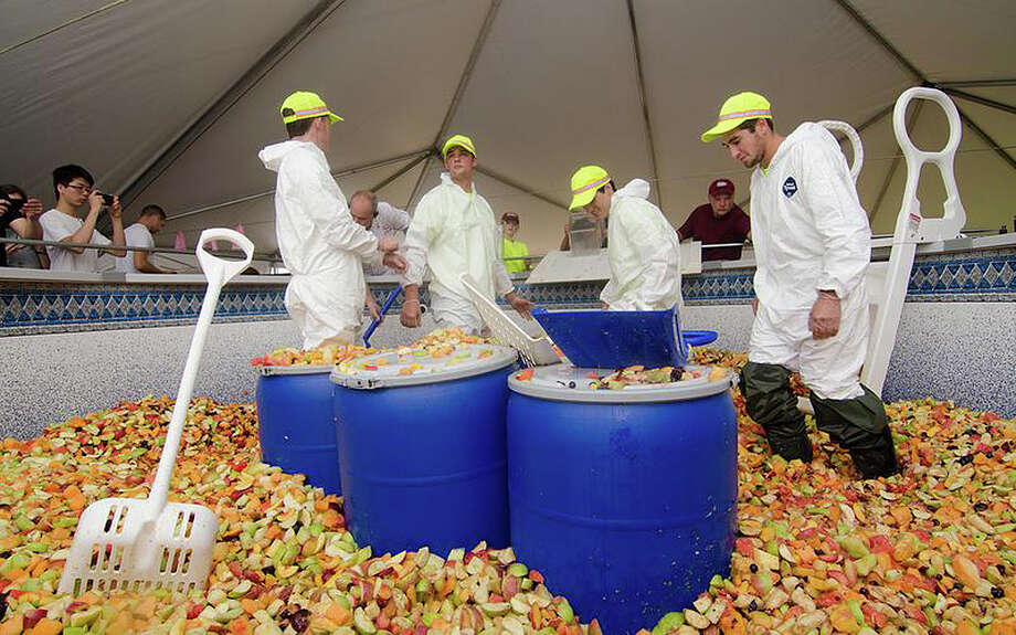 A fruit salad is prepared on  the University of Massachusetts, Amherst, campus, weighing more than 15,000 pounds, on Sept. 2, 2013. A Guinness World Records representative certified the big salad as a record. Photo: Associated Press / University of Massachusetts, Amh