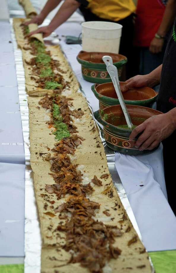 Mexican cooks make a 164 foot-long taco at Garibaldi Square in Mexico City, on Sept. 22, 2011, in the framework of the 2nd Taco Festival, in an attempt to break a record of the longest taco of the world. Photo: RONALDO SCHEMIDT, AFP/Getty Images / 2011 AFP