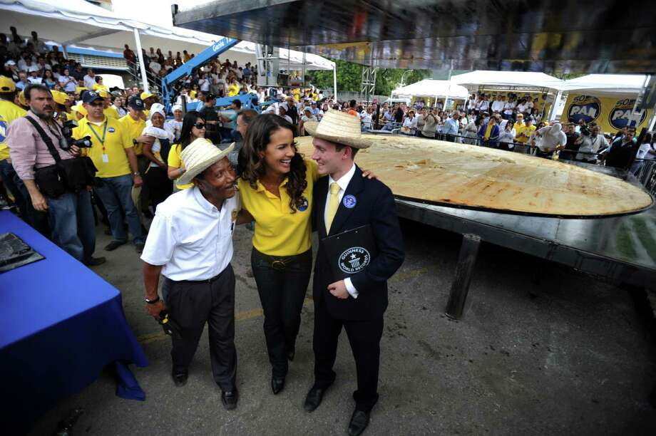 "Venezuelan actress Norelis Rodriguez (center) speaks whit Ralph Hannah (right), Guinness World Records representative in front of a huge arepa (a Venezuelan corn cake) made to set a record, in Caracas, Venezuela, on March 23, 2011. Venezuelan food giant Empresas Polar on Wednesday broke the Guinness record for the ""world's biggest arepa"", after making one of these traditional corn cakes weighing 1,087 pounds and with a nearly 20 foot-diameter, company officials said. Photo: JUAN BARRETO, AFP/Getty Images / 2011 AFP"