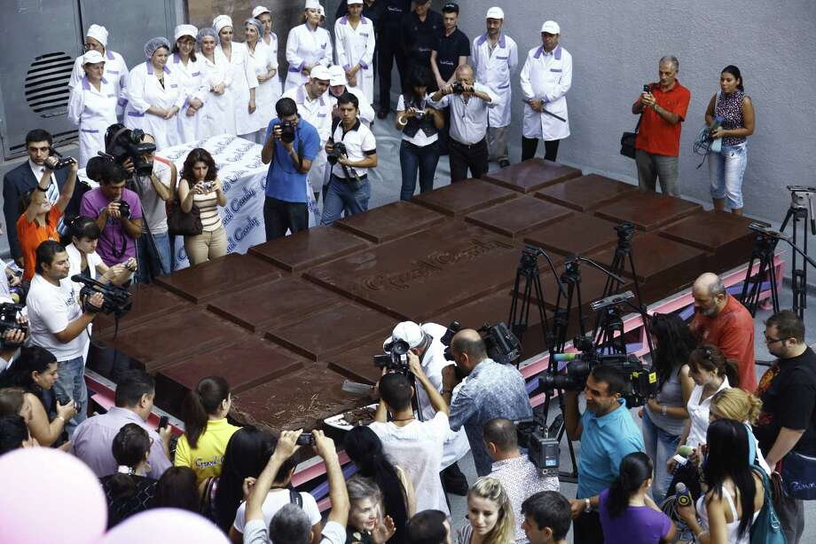 Journalists inspect the world's biggest chocolate brick in Yereven, Armenia, on Sept. 11, 2010.  The Armenian Company broke the Guinness World Record for biggest chocolate bar weighing nearly 9,723 pounds. The bitter chocolate bar measuring 18.4 x 9 x 0.8 feet was manufactured in accordance to traditional technology, using Ghana-imported cocoa beans. Photo: DAVID HAKOBYAN, AFP/Getty Images / 2010 AFP