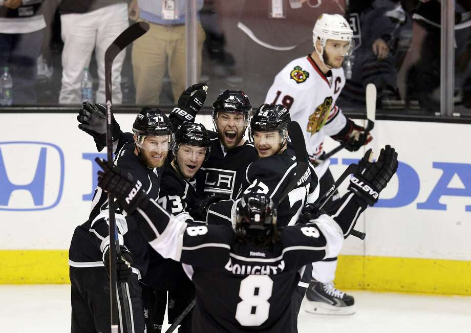 Los Angeles Kings' Jeff Carter (77), Tyler Toffoli (73), Jake Muzzin (6), Dustin Brown (23) and Drew Doughty (8) celebrate a goal by Muzzin as Chicago Blackhawks' Jonathan Toews (19) skates behind them during the first period of Game 4 of the Western Conference finals of the NHL hockey Stanley Cup playoffs on Monday, May 26, 2014, in Los Angeles. (AP Photo/Jae C. Hong) Photo: Jae C. Hong, Associated Press