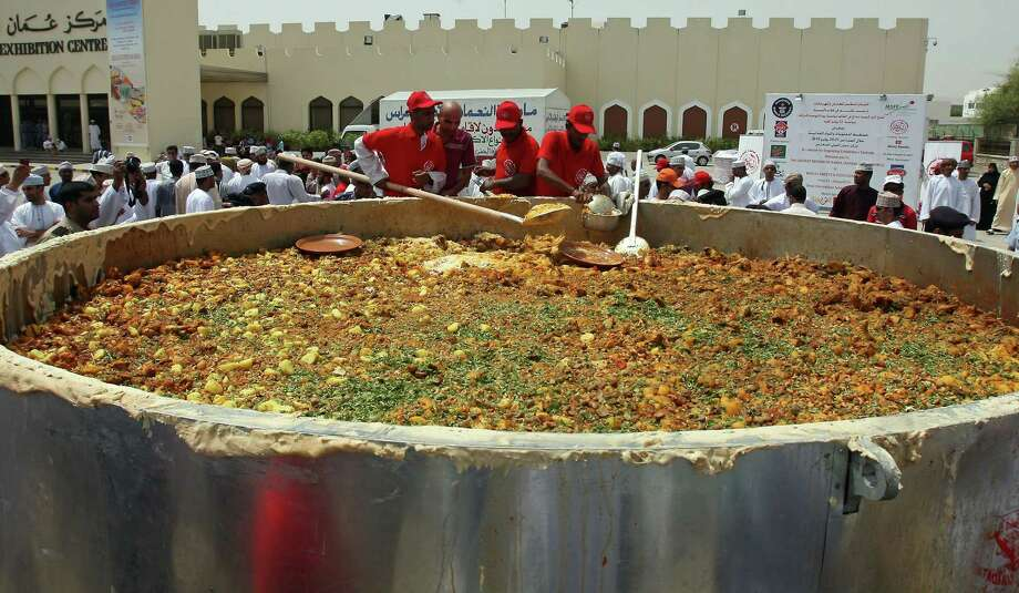 "Omani men stir ingredients in a large pot as they prepare the traditional ""Kabsa"" dish in an attempt to set a new Guinness World Record in Muscat on July 23, 2010. Photo: MOHAMMED MAHJOUB, AFP/Getty Images / 2010 AFP"