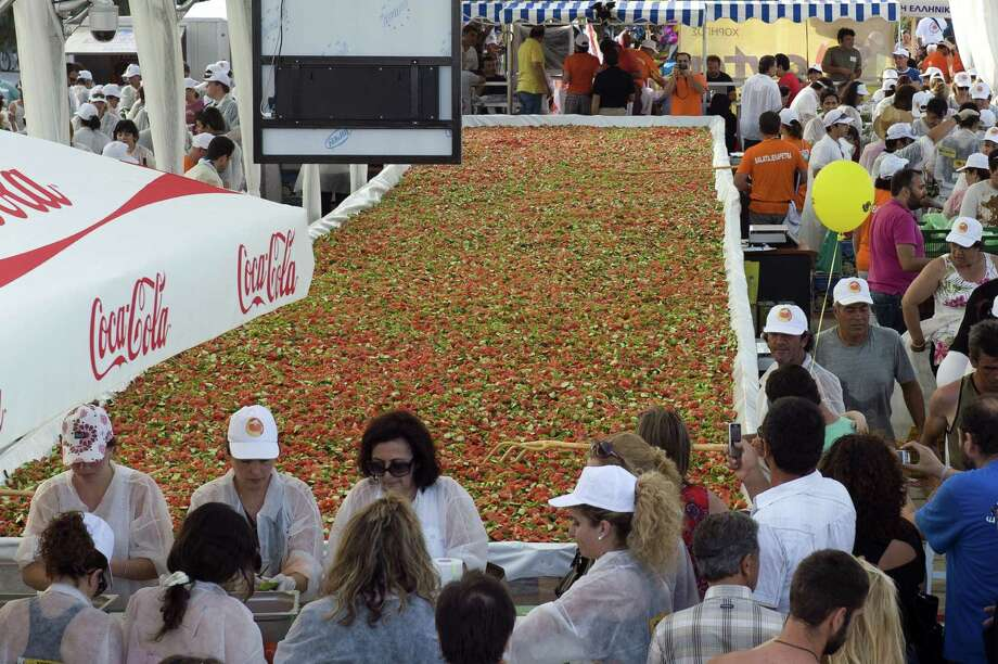 Locals prepare the world's largest tomato salad in Ierapetra on the Greek island of Crete on June 19, 2010. The 11-ton salad is an attempt to break the Guinness World Record of the largest salad in the world. Photo: COSTAS METAXAKIS, AFP/Getty Images / 2010 AFP
