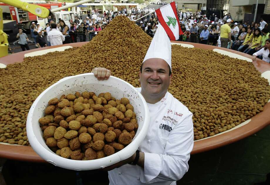 Lebanese chef Ramzi Choueiry holds a bucket of fried falafel balls before adding them to a larger plate in an attempt to set a new Guinness world record in Beirut on May 9, 2010. A day after regaining the world record for the largest plate of hummus, Lebanon set a new record for the largest serving of falafel that weighed about 11,400 pounds. Photo: ANWAR AMRO, AFP/Getty Images / 2010 AFP