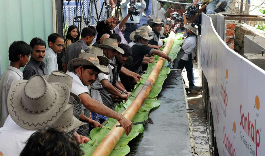 Indian cooks lift a 32.5 foot-long Dosa at Sankalp Resteraunt in Ahmedabad, India, on Aug. 19, 2009. The dosa, which took some 16 cooks to prepare, has exceeded the establishments existing Guinness World Record of 30 feet which was made in February 2006.  Dosa is basically a crepe made from rice and black lentils. It is a typical South Indian dish, eaten for breakfast or dinner, and is rich in carbohydrates and protein. Photo: SAM PANTHAKY, AFP/Getty Images / 2009 AFP