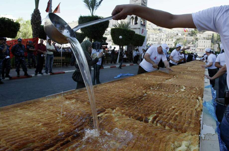Palestinian confectionery makers add the final touches to the world's largest knafeh in the West Bank city of Nablus on July 18, 2009. 170 confectionery makers in Nablus created the knafeh that set a new Guinness record after it measured at 3,891 pounds, 243 feet long and 3.5 feet wide. Knafeh is a sweet pastry made primarily of noodles and honey-sweetened goat cheese that originates from Nablus but renowned throughout the Arab world. Photo: JAAFAR ASHTIYEH, AFP/Getty Images / 2009 AFP