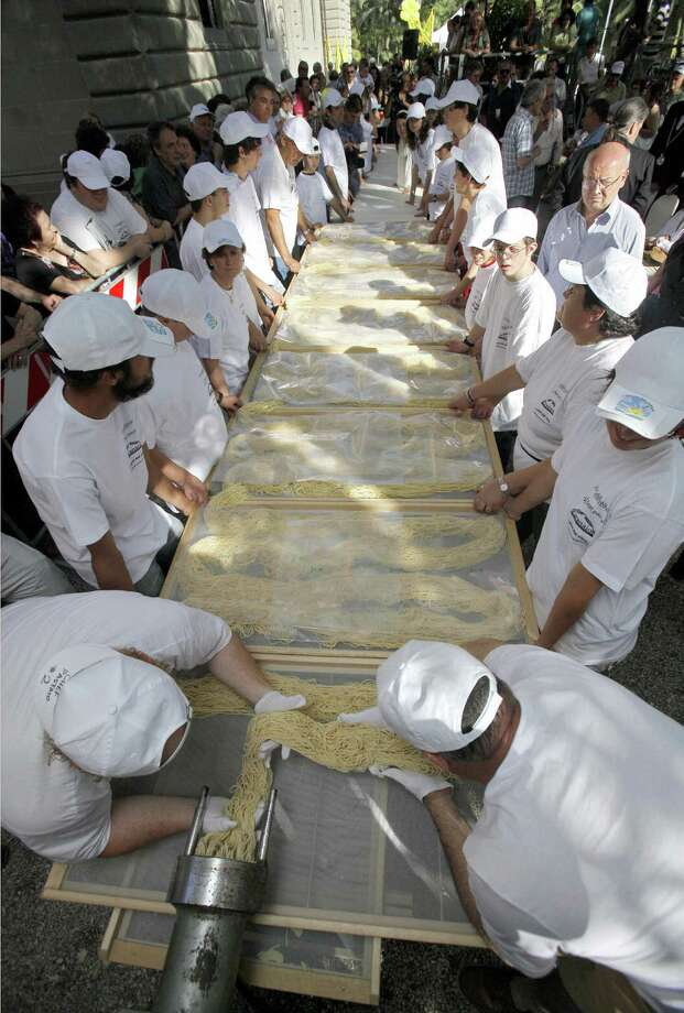 Pasta makers attempt to beat a new Guinness world record for the longest Spaghetti pasta on May 23, 2009, in Capezzano Pianore, central Italy.  More than 771.6 pounds of paste were used to attempt to reach spaghetti of nearly 1 3/4 miles long. The actual record belongs to the Chinese town of Zhengzhu with a 1/4 mile-long rice spaghetti paste. Photo: FABIO MUZZI, AFP/Getty Images / 2009 AFP