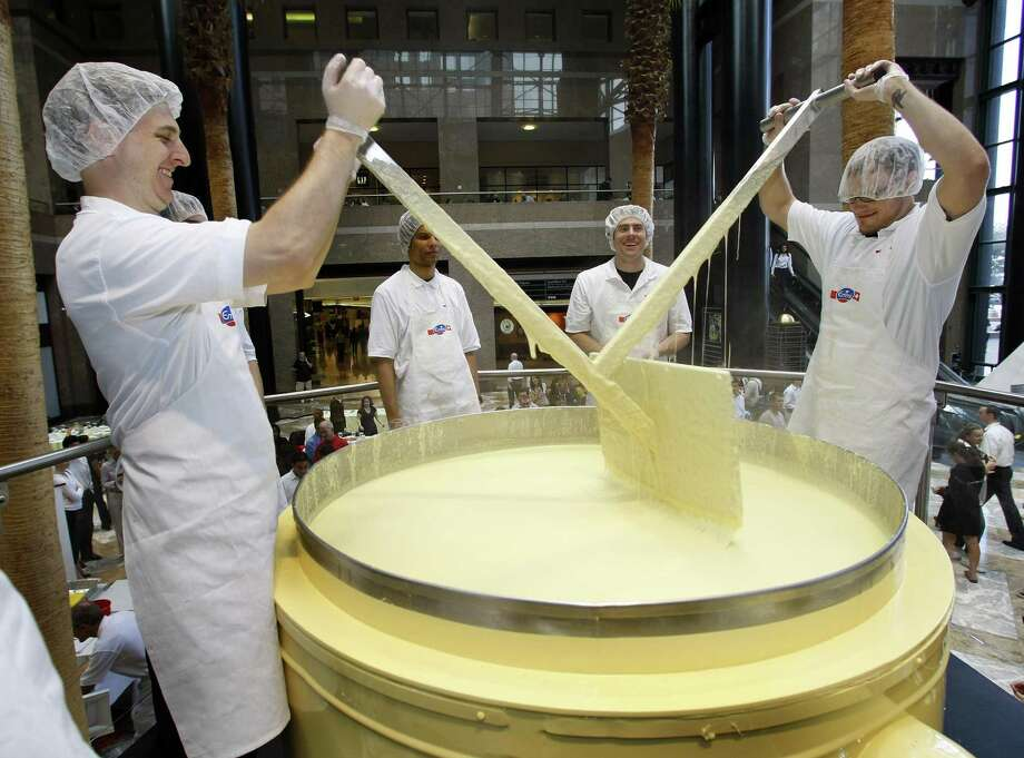 Workers for Emmi, the leading Swiss company for cheese, stir up the World's Biggest Fondue  in New York's Winter Garden on Oct. 3, 2007, dishing out a record 2,866 pounds of hot cheese. Emmi says the fondue will serve about 3,000 people. Photo: TIMOTHY A. CLARY, AFP/Getty Images / 2007 AFP