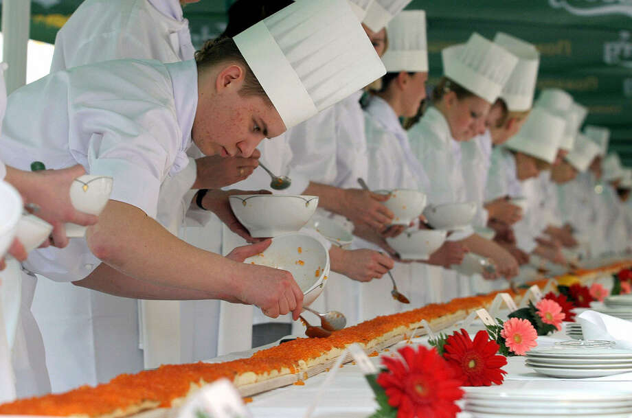 Cooks put red caviar on a 426.5-foot caviar sandwich to attempt a Guinness World Record in front of Grand Europa Hotel in St. Petersburg, Russia, on May 12, 2005, to celebrate the 130th annivesary of the hotel. Photo: YEVGENY ASMOLOV, AFP/Getty Images / 2005 AFP