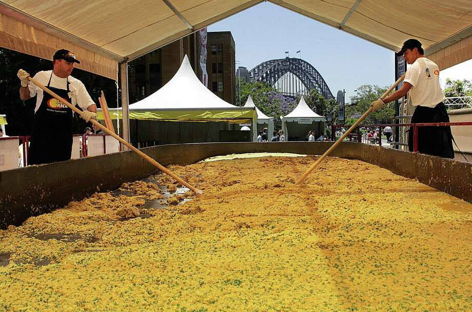 Cooks Nick Roberts (left) and Vincent Nguyen (right) stir the world's largest risotto by the shores of Sydney Harbour, Australia, on Nov. 26, 2004, to celebrate the United Nations International Year of Rice and to raise much needed funds for CARE Australia's campaign against world hunger. The record-breaking recipe called for 3,527.4 pounds of risotto rice, 1,763.7 pounds of peas, 705.5 pounds of butter, 705.5 pounds of Parmesan cheese and 21 gallons of olive oil. Photo: TORSTEN BLACKWOOD, AFP/Getty Images / 2004 AFP