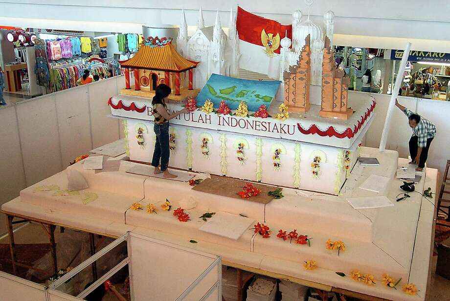Indonesian workers put the finishing touches to a 26.2 feet by 19.7 feet wide and 16.4 feet high cake from Chinese Indonesian woman Nila Sari (not pictured) at a shopping mall in Jakarta on Sept. 30, 2004, for peace and for united Indonesia. Photo: CHOO YOUN-KONG, AFP/Getty Images / 2004 AFP