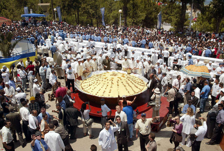 Algerian cooks put the finishing touches to their world's largest couscous on June 3, 2004, at Algiers Fair, during an attempt to break the record. Eighty cooks took part in the attempt, preparing 14,330 pounds of couscous from 4,850 pounds of mutton, in order to serve some 22,000 meals. Photo: HOCINE ZAOURAR, AFP/Getty Images / 2004 AFP