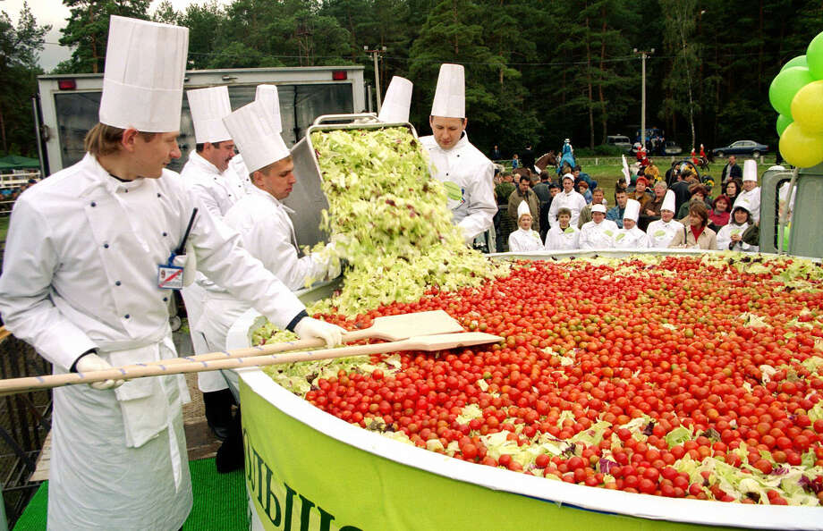 Cooks mix a giant salad in the village of Kotelniki, outside Moscow, Russia, on Sept. 6, 2003. When all the chopping and mixing is done, the concoction of cucumbers, tomatoes, lettuce and herbs is expected to weigh in at 5,732 pounds and make it into the Guinness Book of Records, the ITAR-TASS news agency reported. The mixing, incidentally, will be done with wooden spoons the size of human beings and in a plastic bowl with a diameter of 9.8 feet at the village of Kotelniki, it said. The current world salad record belongs to residents of the Polish town of Pleszew, who mixed a 3,005-pound vegetable salad, the news agency said. Photo: AFP, AFP/Getty Images / 2003 AFP