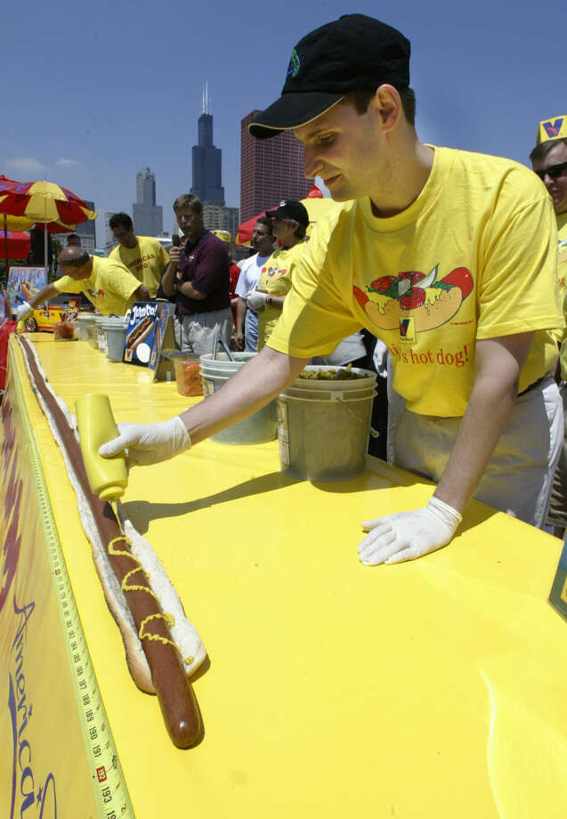 Muatard is applied to the world's longest hot dog, which measures 16 feet, 1 inch, at Buckingham Fountain in Grant Park, Chicago, Ill., on July 2, 2003. Photo: JEFF HAYNES, AFP/Getty Images / 2003 AFP