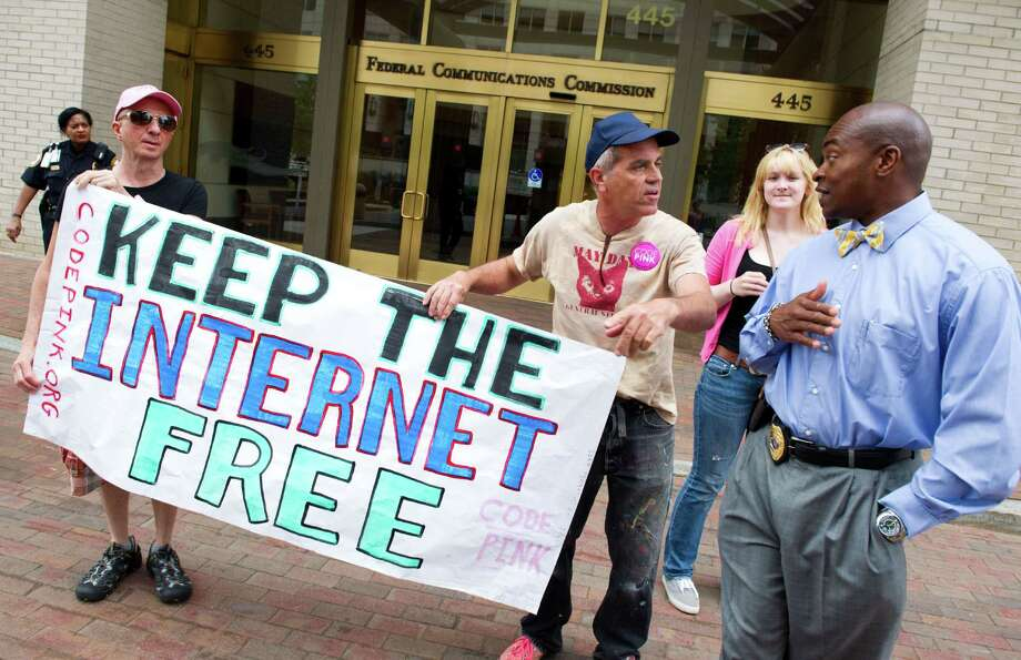 """Protesters hold a rally to support """"net neutrality"""" and urge the Federal Communications Commission (FCC) to reject a proposal that would allow Internet service providers such as AT&T and Verizon """"to boost their revenue by creating speedy online lanes for deep-pocketed websites and applications and slowing down everyone else,"""" on May 15, 2014 at the FCC in Washington, DC. The FCC commissioners voted on a proposal for protecting an open Internet.   AFP PHOTO / Karen BLEIERKAREN BLEIER/AFP/Getty Images Photo: KAREN BLEIER, Staff / AFP"""