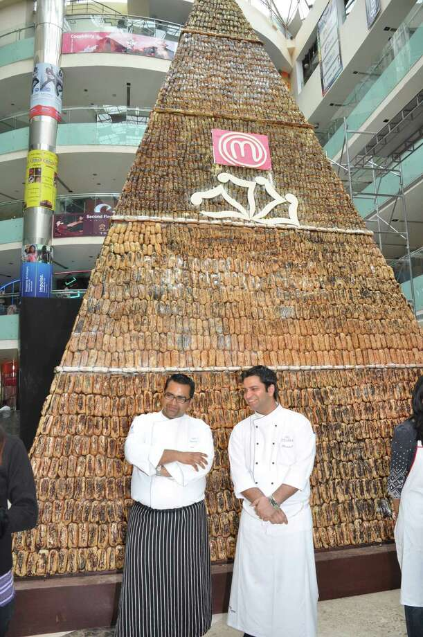 Chefs stand in front of a giant chocolate eclair on display at the Ambience Mall on Nov. 25, 2010, in Gugroan, on the outskirts of New Delhi, India. The 26 foot-tall massive eclair is more than 8 feet long and made in the shape of a pyramid. It has entered Limca Book of Records, a record book of Indian origin. It took 72 hours for the top 12 contestants of a cookery show, Master Chef India and more than two dozen chefs from Leela Kempinski hotel to achieve this amazing feat. The eclair contains more than 264 gallons of milk, 1000 litres of milk, 1,764 pounds of flour, 1,102 pounds of butter, nearly 1,000 pounds of chocolate and as many as 20,000 eggs. Photo: Barcroft Media, Getty Images / Barcroft Media