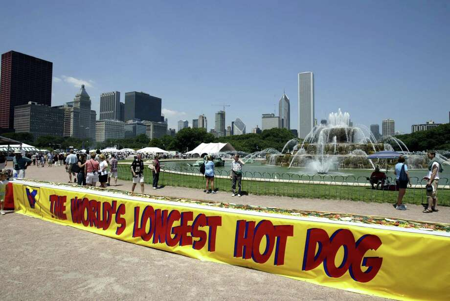 A hotdog billed as the world's longest, measuring a whopping 37 feet, 2 inches, is shown July 1, 2004, in Chicago, Ill. Chicago-based Vienna Beef held the event as part of National Hotdog Month at the Taste of Chicago. The 17 1/2-pound hotdog was set in a bun, dressed with one gallon each of mustard and relish, 140 tomato slices, four pounds of chopped onions, 70 Vienna Kosher pickle spears and 140 sport peppers. Photo: Getty Images / 2004 Getty Images