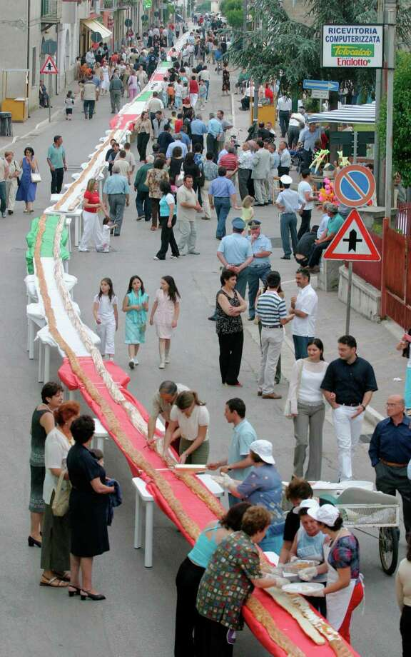 Villagers walk along tables in preparation for a 3,281-foot sandwich as they try to set a new Guinness World Record on June 1, 2003, in Pastoano, Italy. The longest sandwich will use 2,205 pounds of bread, jam, mozzarella cheese, sausages, vegetables and Nutella. Photo: Salvatore Laporta, Getty Images / Getty Images