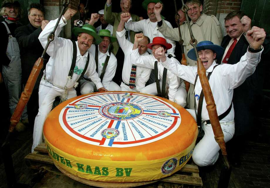 Men from the traditional Alkmaar Cheese Weighing House celebrate their record 1,250-pound Dutch cheese on April 27, 2002, that entered the Guinness Book of Records in Alkmaar, Netherlands. More than 1,320 gallons of milk were used to produce the gigantic cheese. The record was a feat because the cheese was made according to the ''Beemster'' recipe which is a soft kind of cheese, generating the risk that the cheese would rip during the weighing process. Photo: Michel Porro, Getty Images / Getty Images North America