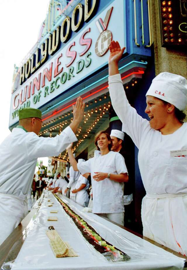 Members of the California Sushi Academy celebrate the making of the world's largest California Roll at the Hollywood Guinness World of Records Museum on Feb. 24, 2000. More than 50 students and chefs from the academy successfully created a 108-foot California Roll that was entered into the Guinness Book of Records. Wrapped in seaweed and composed of rice, crab, avocado and cucumber, the popular food item was created 30 years ago at a sushi bar in the Little Tokyo section of Los Angeles. Photo: Chris Martinez, OnlineUSA Via Getty Images / Hulton Archive