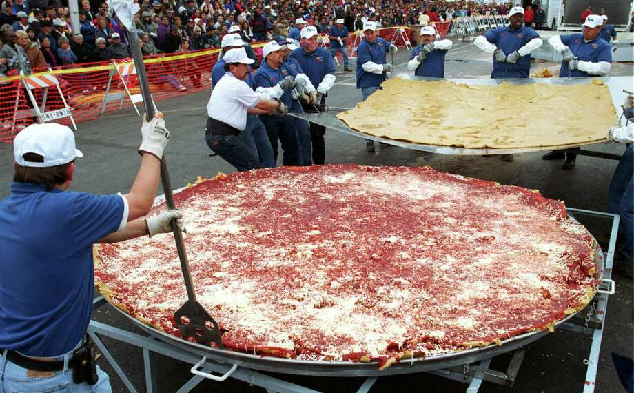 Robert Estrada and others maneuver a tortilla into place on Oct. 8, 2000, as they make an attempt to set the Guinness World Record for the world's largest three-layered enchilada in Las Cruces, N.M. The enchilada measured about 10 feet in diameter and weighed more than 800 pounds. It took about three hours to make. They used 750 pounds of stone ground corn for the three tortillas, 175 gallons of vegetable oil, 75 gallons of red chile sauce, 175 pounds of grated cheese and 50 pounds of chopped onion. Photo: Joe Raedle, Newsmakers Via Getty Images / Hulton Archive