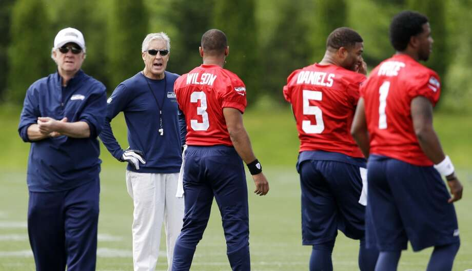 Seattle Seahawks head coach Pete Carroll, second from left, stands near quarterbacks coach Carl Smith, left, as he talks with Seahawks quarterback Russell Wilson (3) at the start of Seahawks OTAs on Tuesday. Photo: Ted S. Warren, Associated Press