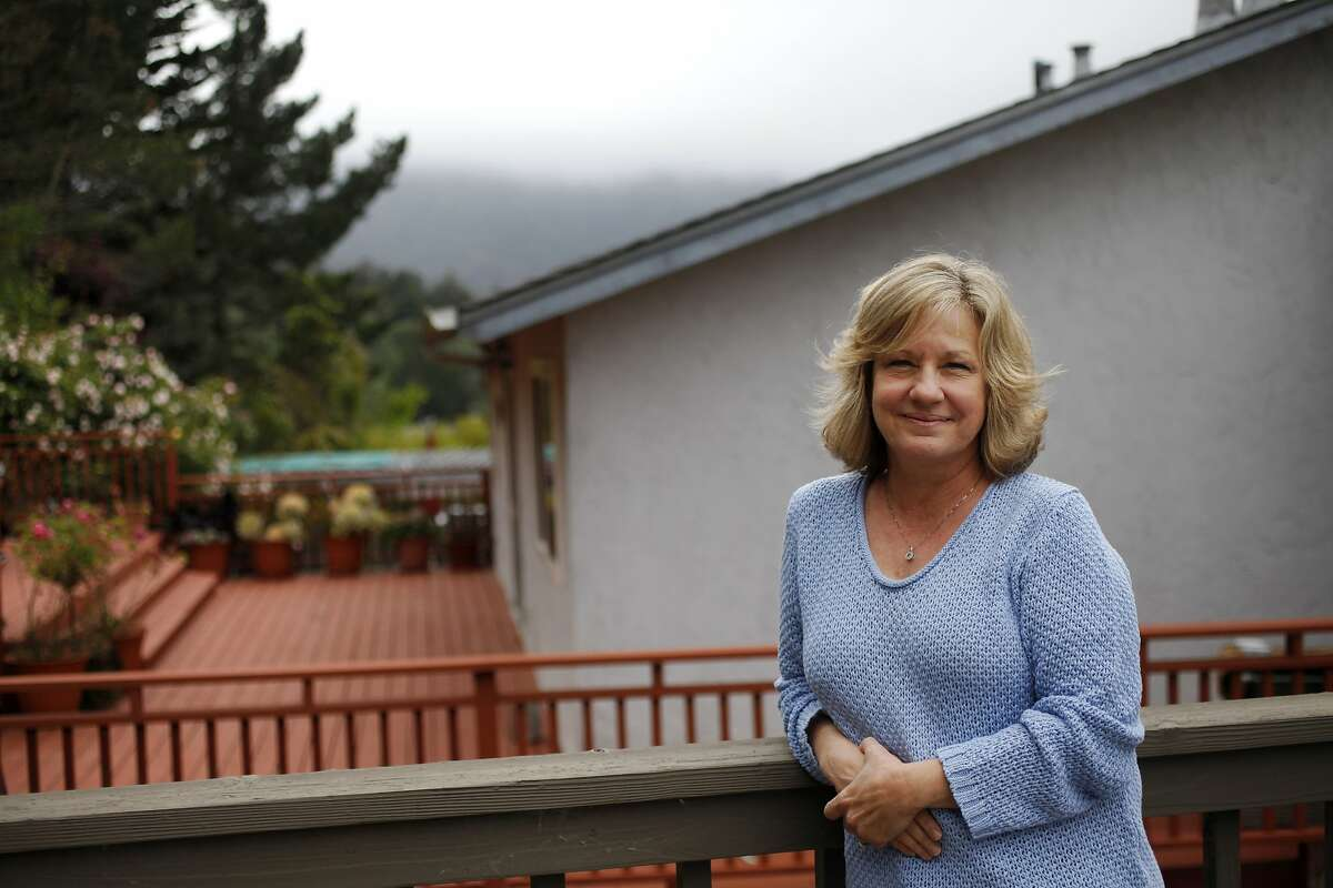 """Lori Madsen pictured on her deck May 17, 2014 at her home in Pacifica, Calif. Madsen caught a flesh-eating disease called necrotizing fasciitis a few years ago after a fall caused her to scrape her arm in a parking lot and it became infected. Her health was deteriorating rapidly and the doctors didn't know how to treat her when, by chance, Dr. John Crew, a vascular surgeon and wound specialist, heard her crying as he was standing at a nurses' station. After meeting her, he deduced that she was suffering from the rare, often fatal disease. Crew treated her with a wound-cleanser called NeutroPhase and he not only saved her arm, """"he saved my life."""" Madsen said."""