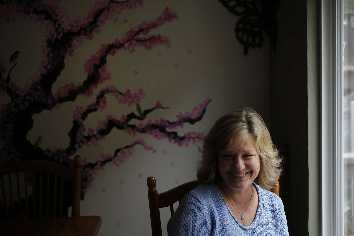 """Lori Madsen pictured in her dining room May 17, 2014 at her home in Pacifica, Calif. Madsen caught a flesh-eating disease called necrotizing fasciitis a few years ago after a fall caused her to scrape her arm in a parking lot and it became infected. Her health was deteriorating rapidly and the doctors didn't know how to treat her when, by chance, Dr. John Crew, a vascular surgeon and wound specialist, heard her crying as he was standing at a nurses' station. After meeting her, he deduced that she was suffering from the rare, often fatal disease. Crew treated her with a wound-cleanser called NeutroPhase and he not only saved her arm, """"he saved my life."""" Madsen said."""