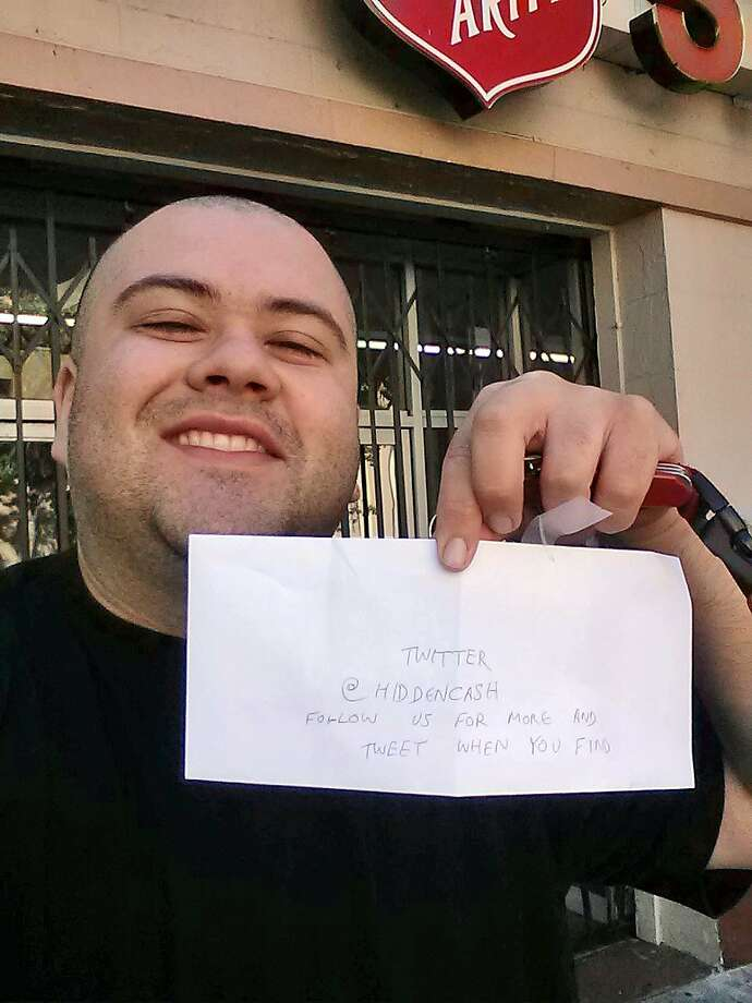 This image provided by Sergio Loza shows Loza holding up an envelope that had cash hidden in it in San Francisco, on Sunday, May 25, 2014. Loza followed the clues from a Twitter user using the handle @HiddenCash to find the money. The mysterious person has been hiding money throughout the city since Friday that's leading scores on a scavenger hunt. Photo: Sergio Loza, Associated Press