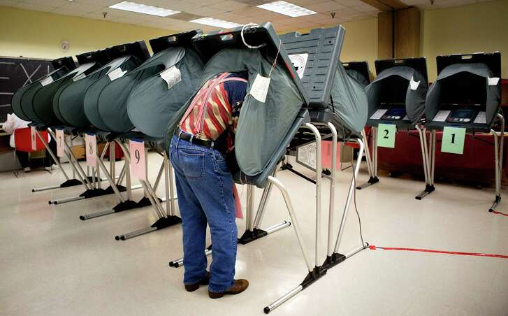 Election Clerk Richard DeLosSantos prepares voting booths at the Metropolitan Multi-Services Center, Tuesday, May 27, 2014, in Houston.