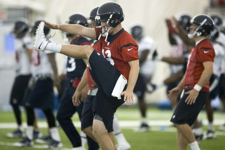 Texans quarterback T.J. Yates (13) kicks while warming up. Photo: Brett Coomer, Houston Chronicle
