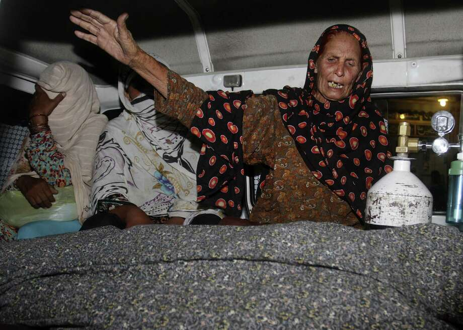 A relative of a woman stoned to death wails over her body in an ambulance in Lahore, Pakistan. Nearly 20 family members, including the woman's father and brothers, attacked her. Photo: K.M. Chaudary / Associated Press / AP