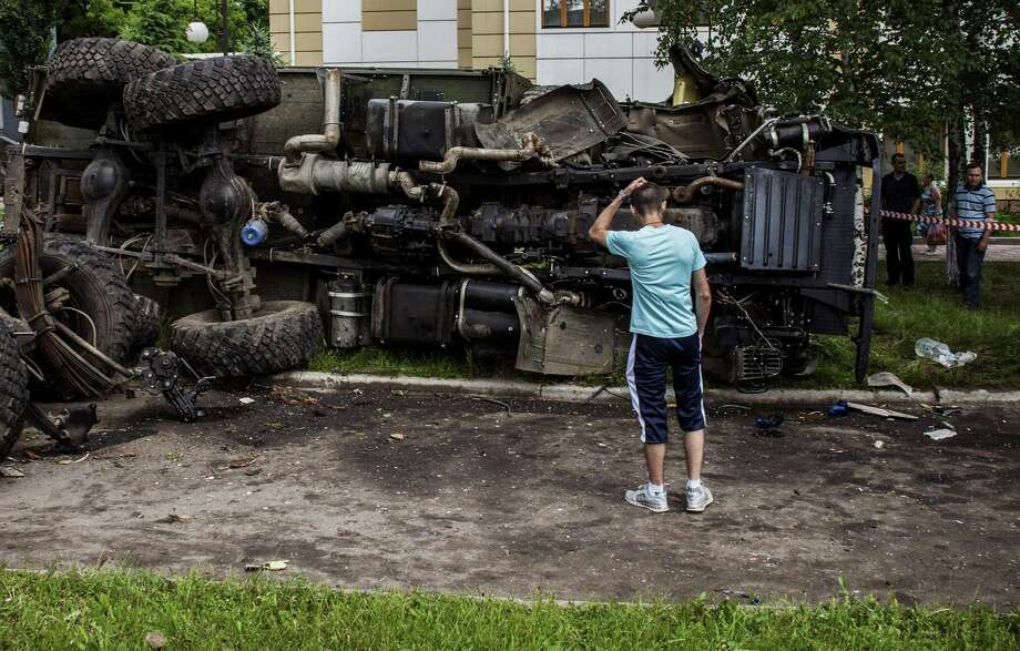 A destroyed truck, previously used by pro-Russian militants and bombed by Ukrainian army soldiers overnight during clashes, lies roadside in the eastern Ukrainian city of Donetsk. Photo: Fabio Bucciarelli / Getty Images / AFP