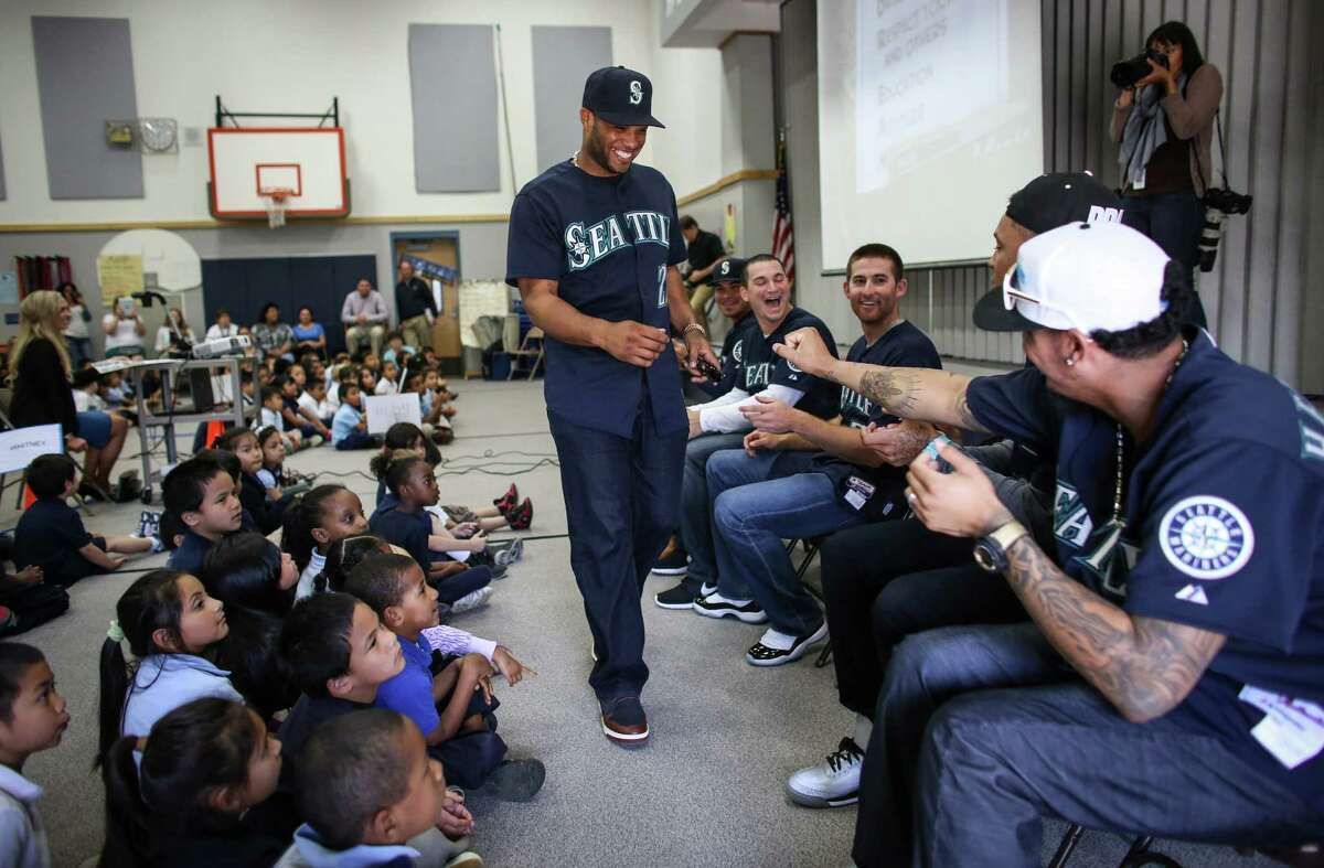 Robinson Cano greets teammates, including Felix Hernandez, right, as Seattle Mariners players visit Hilltop Elementary School in Burien on Tuesday, May 27, 2014. Mariners players Robinson Cano, Felix Hernandez, Brad Miller, Taijuan Walker, Stefen Romero, and Mike Zunino visited the school as part of the D.R.E.A.M. program. The program stresses the principles of being drug-free, respect, education through reading, attitude and motivation to achieve dreams.