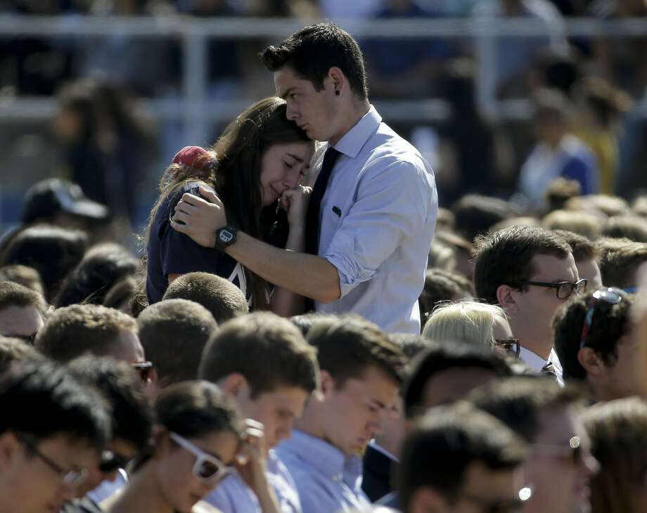 Two people embrace before a service in Harder Stadium at UC Santa Barbara for the victims and families of Friday's rampage in Isla Vista. The six killed were students at the UC campus. Photo: Chris Carlson, Associated Press