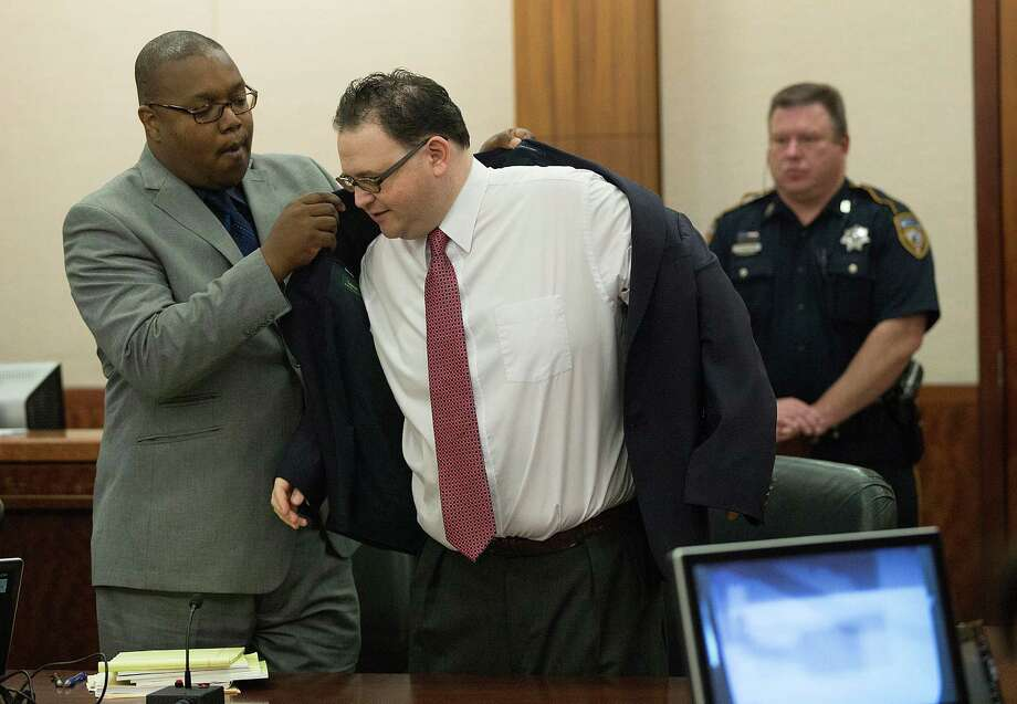 Attorney Eric Davis assists client Mark Augustin Castellano with his jacket before opening statements in his murder trial Tuesday. Photo: Johnny Hanson / © 2014  Houston Chronicle
