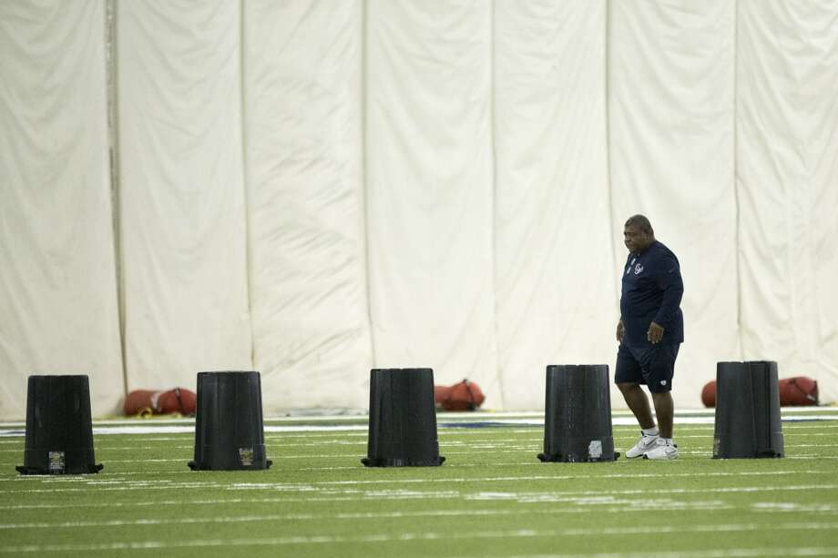 Texans defensive coordinator lines up trash barrels to run a drill. Photo: Brett Coomer, Houston Chronicle
