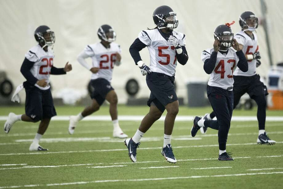Texans linebacker Justin Tuggle (57) and cornerback Elbert Mack (43) run a drill. Photo: Brett Coomer, Houston Chronicle