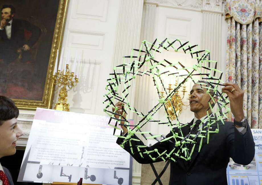 President Barack Obama looks at the science projects of Peyton Robertson, 12, of Fort Lauderdale, Fla., during the 2014 White House Science Fair. Photo: Aude Guerruccip / Getty Images / 2014 Getty Images