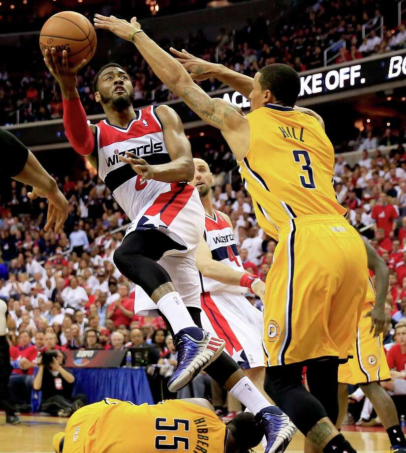 WASHINGTON, DC - MAY 15:  John Wall #2 of the Washington Wizards drives to the basket against Roy Hibbert #55 and George Hill #3  of the Indiana Pacers during Game Six of the Eastern Conference Semifinals during the 2014 NBA Playoffs at Verizon Center on May 15, 2014 in Washington, DC. NOTE TO USER: User expressly acknowledges and agrees that, by downloading and or using this photograph, User is consenting to the terms and conditions of the Getty Images License Agreement. Photo: Rob Carr, Getty Images / 2014 Getty Images