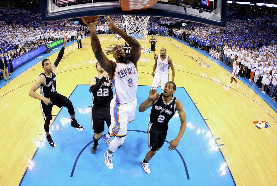 OKLAHOMA CITY, OK - MAY 27: Serge Ibaka #9 of the Oklahoma City Thunder drives to the basket against Kawhi Leonard #2 of the San Antonio Spurs in the first half during Game Four of the Western Conference Finals of the 2014 NBA Playoffs at Chesapeake Energy Arena on May 27, 2014 in Oklahoma City, Oklahoma. NOTE TO USER: User expressly acknowledges and agrees that, by downloading and or using this photograph, User is consenting to the terms and conditions of the Getty Images License Agreement.  (Photo by Ronald Martinez/Getty Images) ORG XMIT: 491979481 Photo: Ronald Martinez / 2014 Getty Images