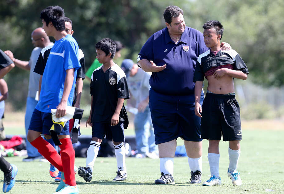 SA International coach James Hope talks with Than Moo at the end of a soccer game for boys in the Rhapsody 66 League at the Rhapsody Soccer Complex last Saturday. Photo: Photos By Marvin Pfeiffer / San Antonio Express-News / EN Communities 2014